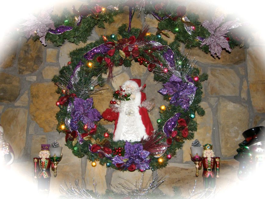 This wreath is  3' in diameter, it has changed several times throughout the years.  I love mixing colors and putting non traditional colors into Christmas.  I started with a plain wreath and added two styles of lights, two ribbons that I sewed together so that both sides would be pretty, flowers and picks.  I hang it from a nail that I put in the frame above the fireplace.  I leave the nail in place all year long because you would have to look hard to see it.