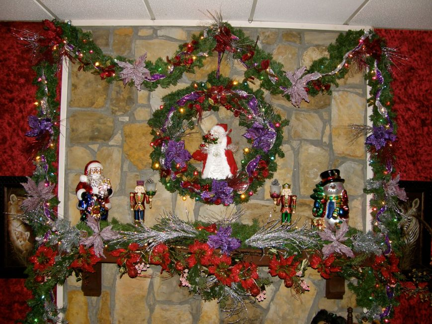 Family Room fireplace.  The snowman and nutcrackers are actually a little shorter, but I put them on top of little bowls, no one will see because they are hidden by all the garland.  So if something isn't working together because of height or proportion, see if you can change it by placing it on top of something.  Books and pretty boxes work good for that if the bottom of the object you want taller will be seen.