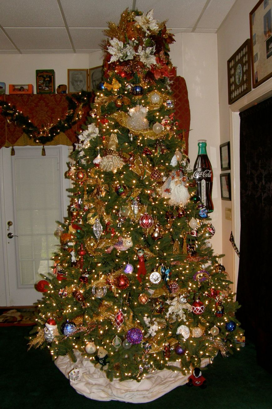 Our family room tree is 10' tall and it is a pain to decorate. I use two ladders so I am not having to move the ladder so many times.  I use fabric as my garland because it is soft and flexible and kind of floats where you want it.  I always have to put the fabric on twice until I get it positioned right.  This tree takes a lot of energy and PATIENCE.  I love color lights, but this tree is for those that only like white lights.  I do love this tree because I buy kooky ornaments for it, so when you see it live it is fun to look at.  It really is much prettier in real life.