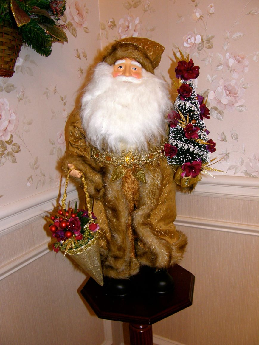 When you buy a decoration like this Santa, if it doesn't match your colors or the style you have in mind.  Buy it and change it.  I added the bead trim, flowers, stems, and berry beads to the tree and to the cone he is carrying.  I also added a little bling to his belt.  Be creative, change things you purchase.