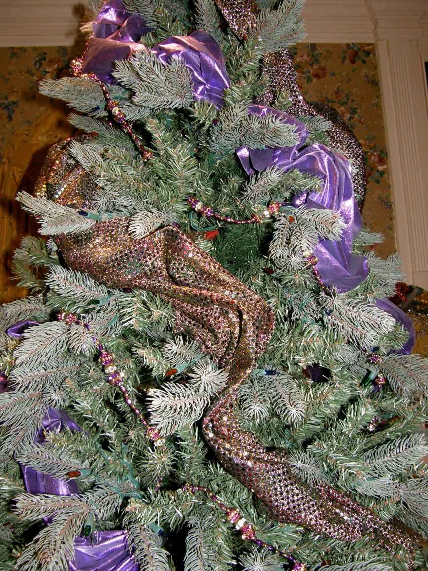 I layer my Christmas trees, the first thing I do after putting my tree up, I cut up fake green garland and place it in the middle of the tree hiding anything that is metal, wires or plugs.  The garland can be stored and reused each year.  On this tree I actually used lighted garland (don't cut it) and wrapped the inside of the tree, the additional lights adds another dimension to the tree.  The next thing I add is the fabric.  On this tree I used purple tissue lame, a multi colored sequin fabric and strands of purchased beads.  I don't like straight lines, so on this tree I draped the fabric at an angle creating little curves while circling the tree.