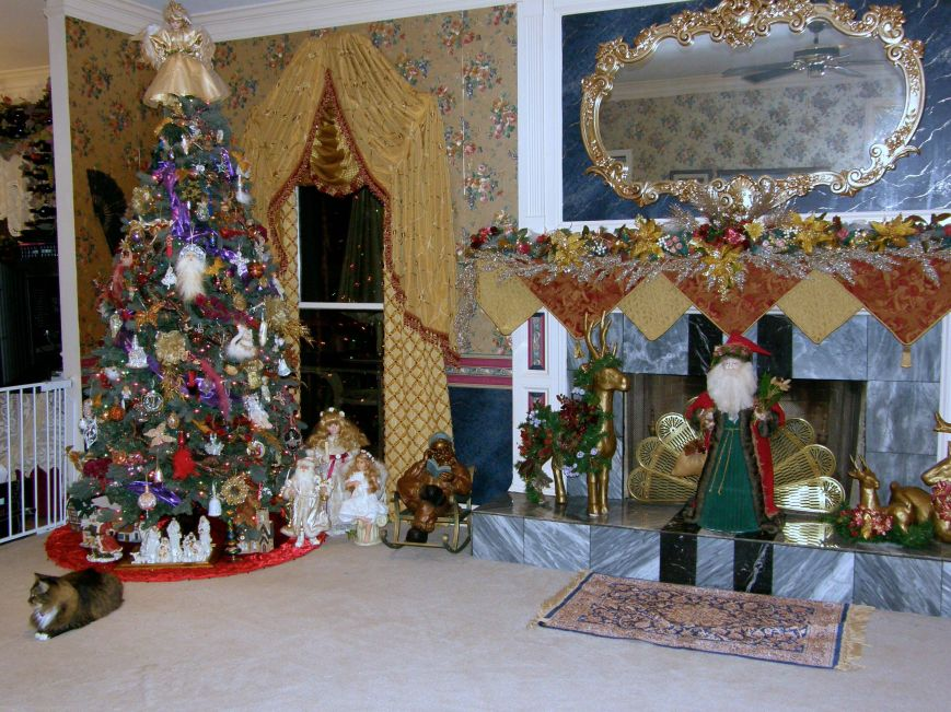 This is my living room tree and fireplace.  I decorate this tree with a little bit of a Victorian feel.  The reindeer on the fireplace are those brown papier-mâché deer you find at craft stores.  I spray painted them gold, then decorated them with garland, ribbons, flowers, beads, and misc. (The cat is real, LOL)