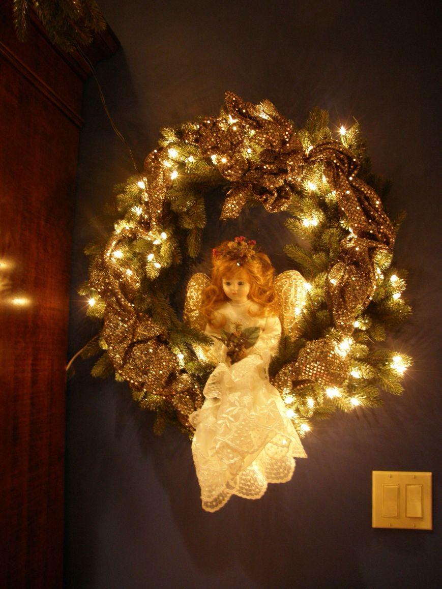 This wreath was bought with the lights already on it.  I collect porcelain dolls, so I took one of the them and turned her into an angel.  I handed beaded wings I made, made a dress out of lace and added flowers.  The gold is a sequin fabric that I just weaved in and out of the wreath limbs.  I have made different types of wreaths that I have placed throughout the house.  I did not take pictures of all of them.  Wreaths are easy to make, just buy a plain wreath, add lights if you want (most of my wreaths do not have lights), add flowers, stuffed animals, floral picks, toys, dolls, ornaments, or whatever you want to.  You can do themes, if you want, like in my kitchen I found cookie ornaments that I used along with ribbon and baby breaths.  It looks real cute in my kitchen.